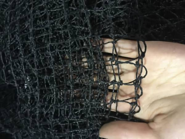 Black knotted debris netting on a women's hand.
